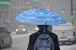 Philadelphia, PA, USA - February 20, 2019: A man holding a blue sky umbrella walks on Market Street as commuters get an early jump on rush hour as winter storm Petra brings several inches of snow to the Philadelphia region, on February 20, 2019. To accommodate, SEPTA implemented its Early Exit Schedule, running nine Regional Rail trains hours ahead of their normal schedules.
