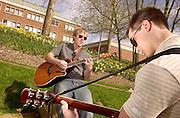 16370Spring Campus Shots 4/6/04                          .. Thomas Taylor, left and    Joe Goryance(far right) play guitar at emeriti park 4/6/04