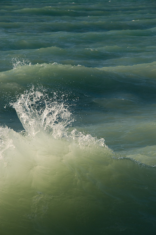 A wave breaks on Lake Michigan, near Sleeping Bear Dunes and the Point Betsie Lighthouse.