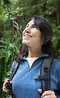 Middle-aged woman in forest looking up smiling