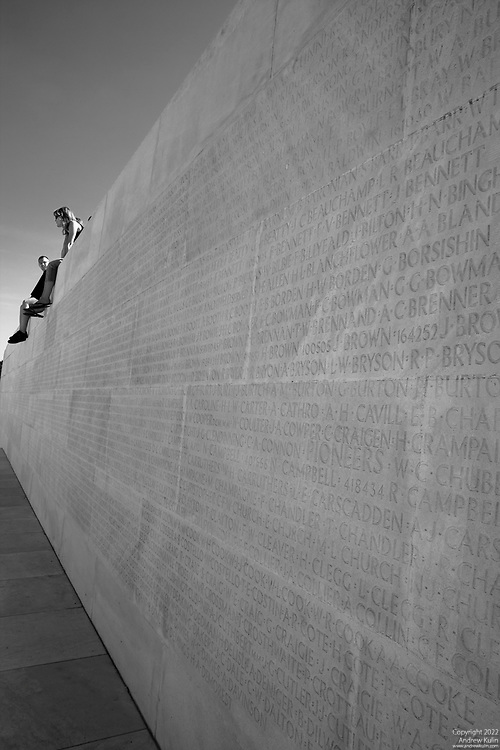 Black and White image of young persons relaxing at the wall of the names of the missing at the Canadian War Memorial at Vimy Ridge in France.2592x3888 (original size)