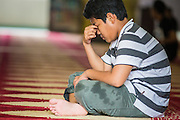 22 DECEMBER 2012 - SINGAPORE, SINGAPORE:  A teenaged boy prays in the main prayer hall at the Sultan Mosque in Singapore. The Sultan Mosque is the focal point of the historic Kampong Glam area of Singapore. Also known as Masjid Sultan, it was named for Sultan Hussein Shah. The mosque was originally built in the 1820s. The original structure was demolished in 1924 to make way for the current building, which was completed in 1928. The mosque holds great significance for the Muslim community, and is considered the national mosque of Singapore. It was designated a national monument in 1975.           PHOTO BY JACK KURTZ