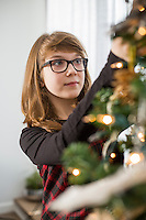 Teenage girl decorating Christmas tree at home
