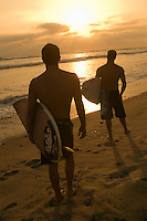 Two surfers standing on beach holding surfboards watching sunset back view