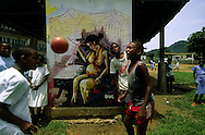 Children playing football (soccer) in front of a painted wall with a mural about how to protect pregnant women from malaria.