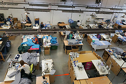 © Licensed to London News Pictures. 21/04/2020. Dukinfield, UK.   A view of workers   as staff at Tibard begin working around the clock on an order of 5,000 units of nurses  uniforms (scrubs) for NHS workers per week in Dukinfield , owing to growing demand during the COVID-19 pandemic. The factory typically manufactures uniforms for the catering industry.  Photo credit: Ioannis Alexopoulos /LNP