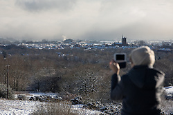 © Licensed to London News Pictures . 23/01/2019. Bolton , UK . A woman takes photos of the landscape on a mobile phone from Horrocks Wood . Clear skies and snow shrouds the hills in the North West as fog descends over Manchester City Centre . Photo credit : Joel Goodman/LNP