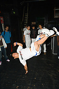 A dancer in white dancing and standing on his right hand. UK B-Boy championships 06. 08/10/2006