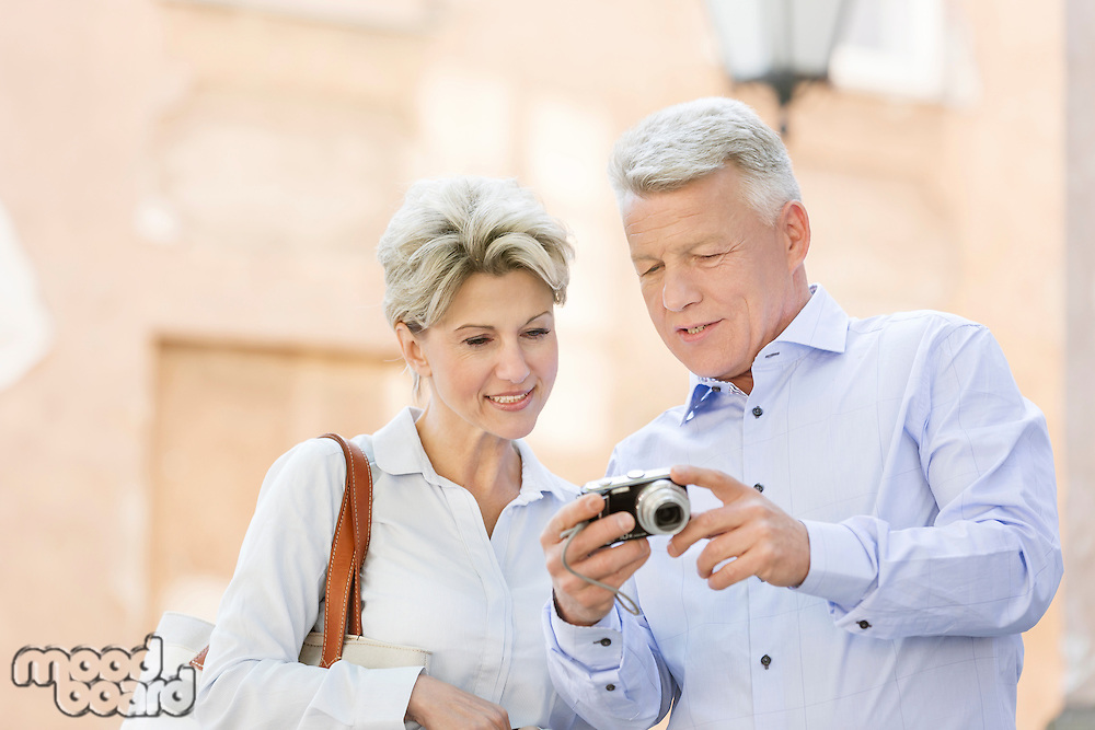 Smiling middle-aged couple reviewing photos on digital camera outdoors