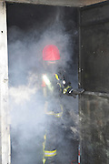 Firefighters with protective equipment in a smoke filled room
