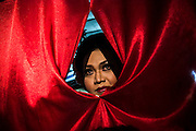 Yeyen watches her friends perform on the stage through a curtain during a show in Mojokerto, East Java, Indonesia.