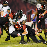 24 November 2018: San Diego State Aztecs linebacker Troy Cassidy (42) tackles Hawaii Warriors running back Miles Reed (26) as the ball is knocked loose and removed by San Diego State Aztecs safety Tariq Thompson (14) in the fourth quarter. The Aztecs closed out the season with a 31-30 overtime loss to Hawaii at SDCCU Stadium.