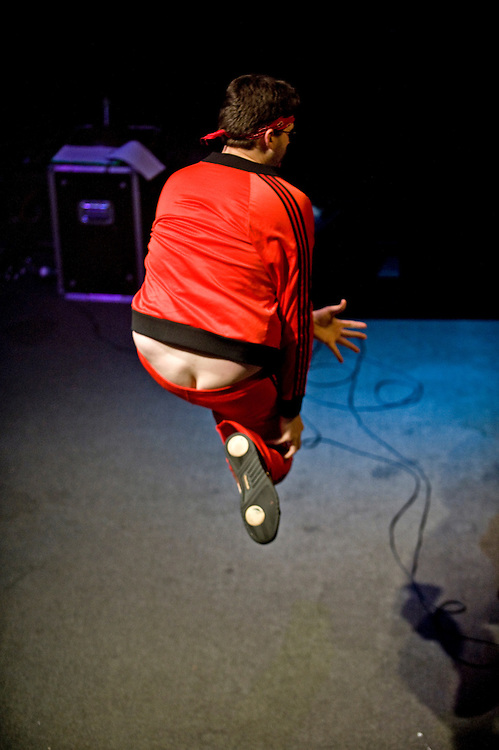 "(staff photo by Matt Roth)..This apparent wardrobe malfunction is all part of Kolb ""Vlad DM Wailer"" Ettenger's stage performance. His tight red track suit jacket eventually comes unzipped, flaunting his beer belly, and he proudly displays his plumber butt to the audience. Kitsch and self defacement is part of the air guitar culture, celebrating the ""dorks"" who never learned to play their own instruments. Ettenger, 23, from College Park, sparked the audience's fire, but the judges felt his technique needed work. He did not advance to the second round of the U.S. Air Guitar Regional Championships at the 9:30 Club in Washington D.C. Friday, May 29, 2009. The national championships will return to the 9:30 Club August 7th."
