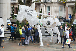 © Licensed to London News Pictures. 16/10/2019. London, UK. Extinction Rebellion march with a large white puppet horse to protest against climate change at Embassies in central London. Activists continue to occupy roads around Westminster for the 10th day as protesters gather in Trafalgar Square to oppose the Police ban. Photo credit: Alex Lentati/LNP