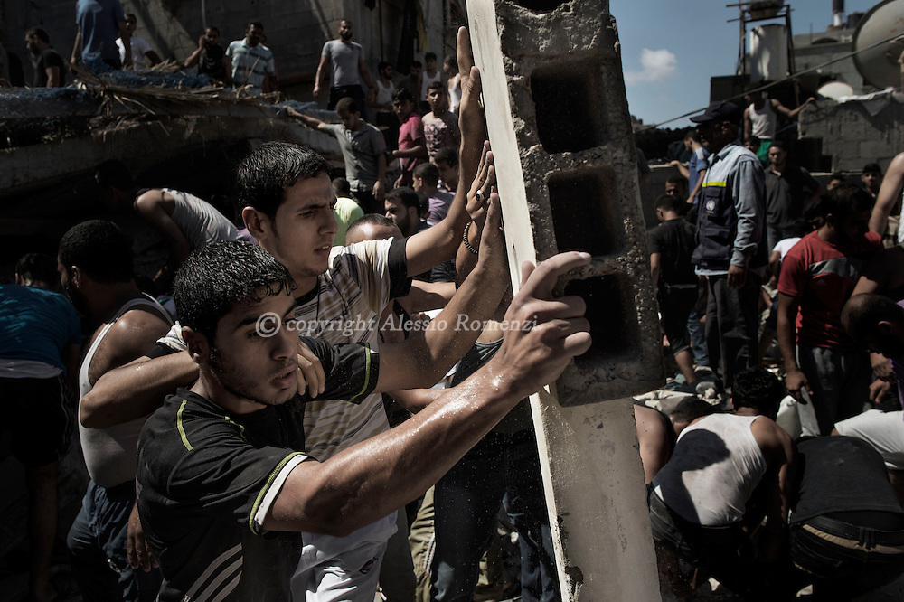 Gaza Strip, Shati refugee camp: Looking for survivors, Palestinians try to remove, with only their hands, rubble of a house in Shati refugee camp in Gaza City, after an Israeli airstrike destroyed it on August 4, 2012. ALESSIO ROMENZI