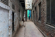 A man standing at the end of a narrow alleyway,  old town, Varanasi
