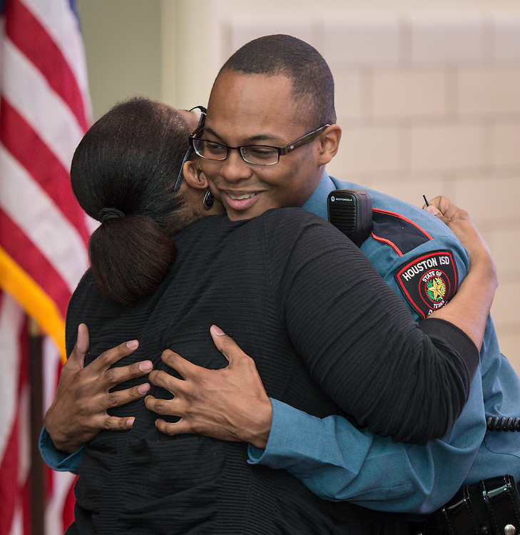 Joshua Clark, right, gets a hug from a family member after receiving his badge during a swearing-in ceremony for new officers at the Houston ISD Police Department, March 3, 2014.