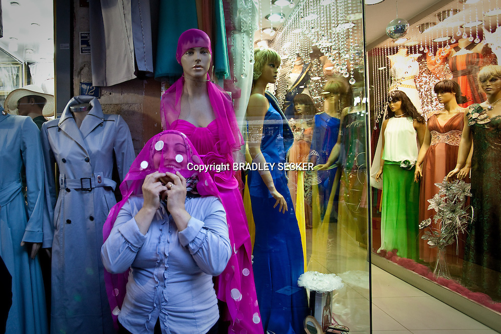 ISTANBUL, TURKEY, JUNE 2012: A salesperson hides her face under the dress of a model, along the enterance to the Grand Bazaar. (Photo by Bradley Secker for the Washington Post)