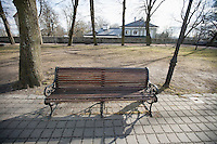 Wooden bench on path in park; Tallinn; Estonia; Europe