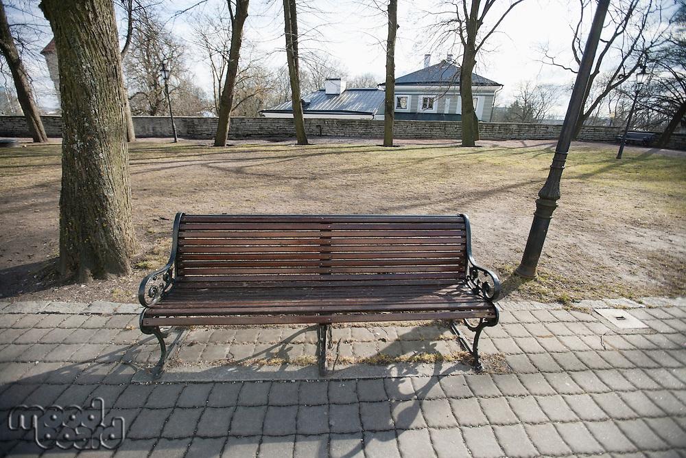Wooden bench on path in park; Tallinn; Estonia; Europe
