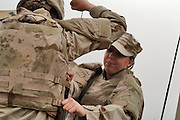 Airman 1st Class Nicole P. O'Hara (right), gives a strong pull body armor adjustment straps on Senior Airman Charity L. Trueblood. They are combat convoy security forces specialist deployed to the 732 Expeditionary Logistics Readiness Squadron, at Balad Air Base, Iraq  (U.S. Air Force photo by Master Sgt. Lance Cheung)<br />