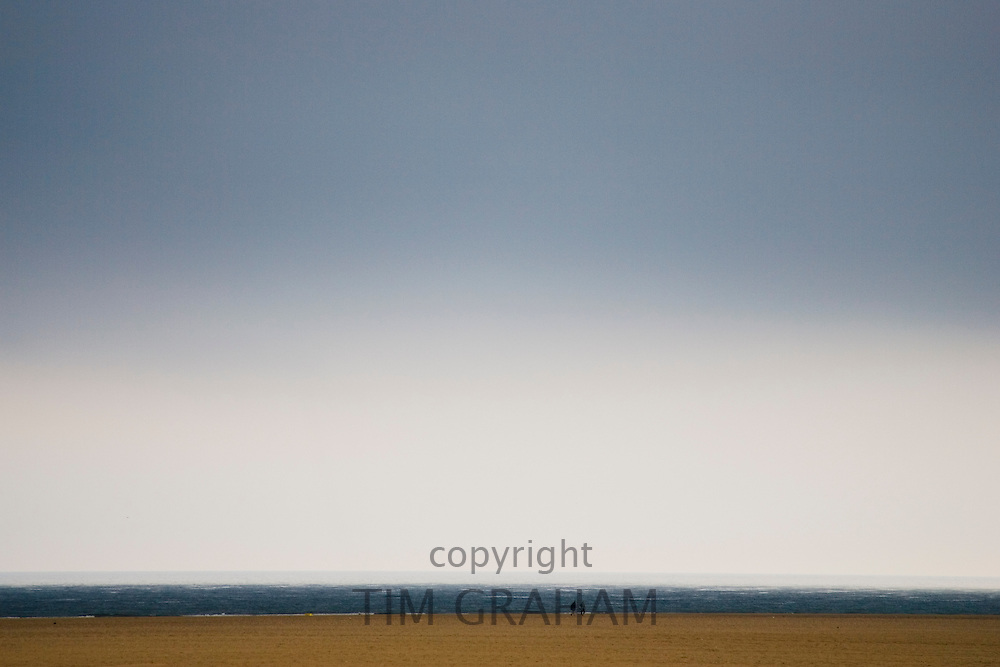 Couple walk along Brancaster Beach, Norfolk, United Kingdom