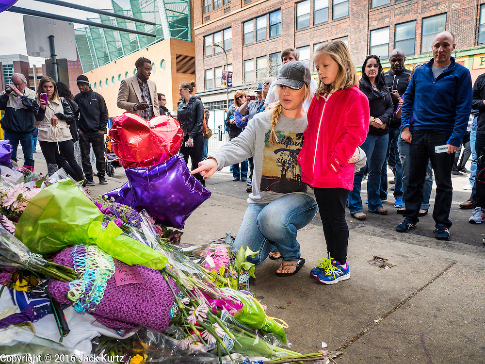 """22 APRIL 2016 - MINNEAPOLIS, MN: A woman and her daughter look at a memorial for Prince at 1st Ave in Minneapolis. Thousands of people came to 1st Ave in Minneapolis Friday to mourn the death of Prince, whose full name is Prince Rogers Nelson. 1st Ave is the nightclub the musical icon made famous in his semi autobiographical movie """"Purple Rain."""" Prince, 57 years old, died Thursday, April 21, 2016, at Paisley Park, his home, office and recording complex in Chanhassen, MN.    PHOTO BY JACK KURTZ"""