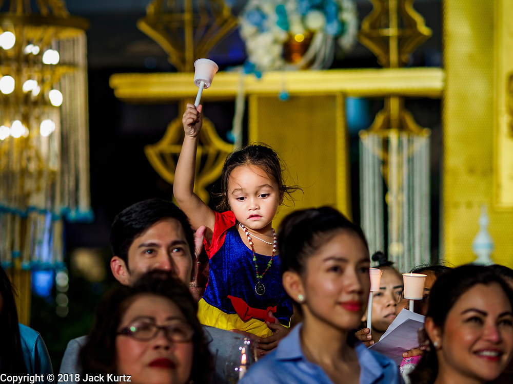 12 AUGUST 2018 - BANGKOK, THAILAND: A child on her father's shoulders during a candlighting ceremony to honor the 86th birthday of Sirikit, the Queen Mother of Thailand at EmQuartier Mall in Bangkok. She was the wife of Bhumibol Adulyadej, the late King, and she is the mother of His Majesty King Maha Vajiralongkorn Bodindradebayavarangkun of Thailand, who succeeded his father. August 12 is also celebrated as Mother's Day in Thailand.     PHOTO BY JACK KURTZ