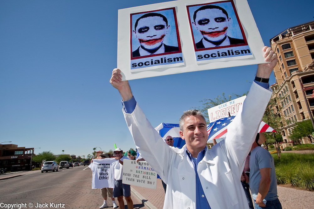 """Aug. 8, 2009 -- SCOTTSDALE, AZ: GREGORY WIRTH, from Scottsdale, carries a sign equating President Obama with the """"Joker"""" during a protest against the Obama health care plan. Nearly 1,000 people opposed to the President Barack Obama's health care reform efforts picketed the offices of Congresman Harry Mitchell (D-AZ) in Scottsdale, AZ, Saturday. The protest was organized by conservative groups who are organizing similar protests against President Obama across the US. Ostensibly concerned mostly with health care reform, it was also a protest against almost everything related to the Obama administration. Photo by Jack Kurtz / ZUMA Press"""