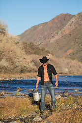 cowboy with an open shirt carrying a bucket by a stream