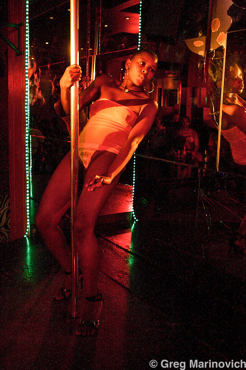 """TIna"" pole dances at the black strip club Malasha in Randburg, Dec 15, 2006. Photo Greg Marinovich"