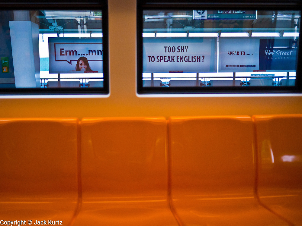14 JULY 2011 - BANGKOK, THAILAND:  An ad for English classes as seen through the window of a BTS Skytrain on the Silom line. The Bangkok Mass Transit System, commonly known as the BTS Skytrain, is an elevated rapid transit system in Bangkok, Thailand. It is operated by Bangkok Mass Transit System Public Company Limited (BTSC) under a concession granted by the Bangkok Metropolitan Administration (BMA). The system consists of twenty-three stations along two lines: the Sukhumvit line running northwards and eastwards, terminating at Mo Chit and On Nut respectively, and the Silom line which plies Silom and Sathon Roads, the Central Business District of Bangkok, terminating at the National Stadium and Wongwian Yai. The lines interchange at Siam Station and have a combined route distance of 55 km.     PHOTO BY JACK KURTZ