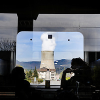 Passengers on a passing train and G&ouml;sgen Nuclear Power Plant (Kernkraftwerk G&ouml;sgen), with smoke rising from its cooling tower. <br />