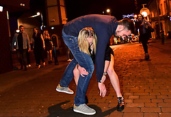 © London News Pictures. 01/01/2017. Aberystwyth, UK. A young woman attempts to pick up a friend while out celebrating the 2017 New Year in Aberystwyth, Wales, UK on January 01, 2017. Photo credit: Keith Morris/LNP