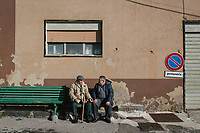 "SUTERA, ITALY - 8 JANUARY 2018: Two residents of Sutera chat on a bench in Sutera, Italy, on January 8th 2018.<br /> <br /> Sutera is an ancient town plastered onto the side of an enormous monolithic rock, topped with a convent, in the middle of the western half of Sicily, about 90 minutes by car south of the Sicilian capital Palermo<br /> Its population fell from 5,000 in 1970 to 1,500 today. In the past 3 years its population has surged  after the local mayor agreed to take in some of the thousands of migrants that have made the dangerous journey from Africa to the Sicily.<br /> <br /> ""Sutera was disappearing,"" says mayor Giuseppe Grizzanti. ""Italians, bound for Germany or England, packed up and left their homes empty. The deaths of inhabitants greatly outnumbered births. Now, thanks to the refugees, we have a chance to revive the city.""<br />  Through an Italian state-funded project called SPRAR (Protection System for Refugees and Asylum Seekers), which in turn is co-funded by the European Union's Fund for the Integration of non-EU Immigrants, Sutera was given financial and resettlement assistance that was co-ordinated by a local non-profit organization called Girasoli (Sunflowers). Girasoli organizes everything from housing and medical care to Italian lessons and psychological counselling for the new settlers.<br /> The school appears to have been the biggest beneficiary of the refugees' arrival, which was kept open thanks to the migrants.<br /> Nunzio Vittarello, the coordinator of the E.U. project working for the NGO ""I Girasoli"" says that there are 50 families in Sutera at the moment."