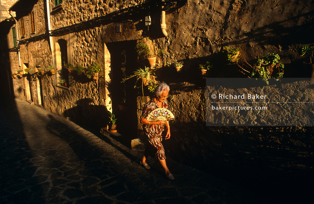 An elderly Spanish lady walks towards a strong setting sun that shines through an old medieval street in the beautiful town of Valldemossa in north-west Majorca, one of the Balearic Island. She leans forward, striding with a quick pace while holding a traditional fan called an abanico. Valldemossa is at 400 kilometres above sea level, the highest community on the island and in the middle of the valley of Sierra de Tramuntana. Part of the village goes up into the mountain slope and sits on the slopes of the Tramuntana mountains. The town gained some sort of fame when Polish composer Frederic Chopin came and stayed at the Carthusian monastery (Cartoixa Reial) with his lover George Sand in the winter of 1838-39.
