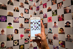 © Licensed to London News Pictures. 01/11/2016. London, UK. A visitor to the 'Hair by Sam McKnight' exhibition at Somerset House takes a photo of an Instagram wall showing images collated from the hair stylist's feed. The show, which runs from 2nd November, 2016 to 12th March, 2017, celebrates the career of fashion's favourite hair stylist. Photo credit: Peter Macdiarmid/LNP