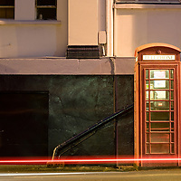 Night shot of UK phonebox with light trails from passing car.