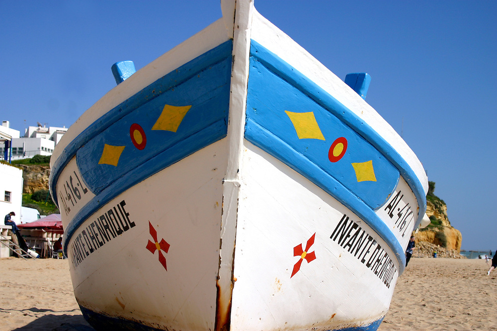 Colourfully painted fishing boat rests on beach, Algarve Portugal