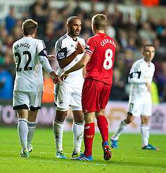 SWANSEA, WALES - Monday, September 16, 2013: Liverpool's captain Steven Gerrard and Swansea City's captain Ashley Williams embrace after the 2-2 draw during the Premiership match at the Liberty Stadium. (Pic by David Rawcliffe/Propaganda)