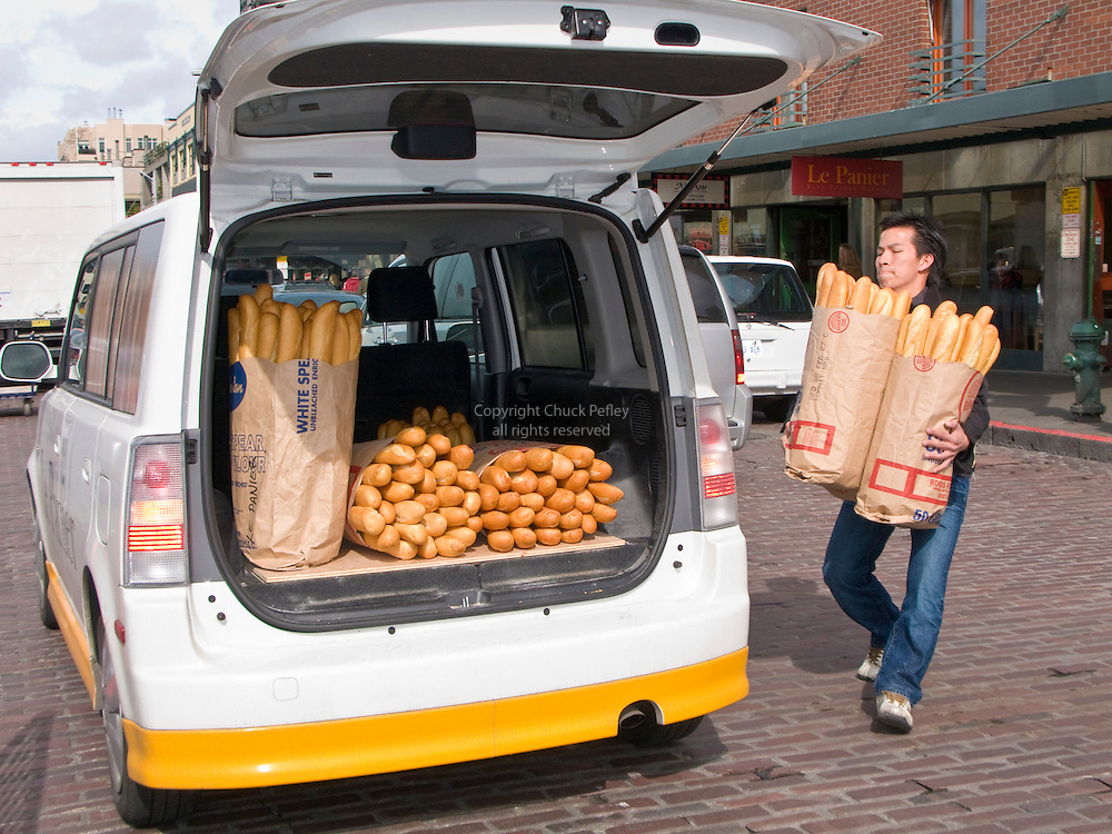 Man loading fresh French bread into delivery vehicle from Le Panier, A Very French Bakery, Pike Place Market, Seattle, Washington