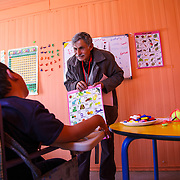 Khalid receives one on one instruction in the Mercy Corps resource room. His volunteer instructor, Ibrahim (also a refugee), has over 35 years of teaching experience in Syria. Zaatari camp for Syrian refugees, Jordan, April 2015.