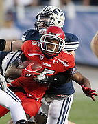 Utah runningback John White (15) attempts to get past BYU linebacker Brandon Ogletree, back, during the first half of an NCAA college football game, Saturday, Sept. 17, 2011, at LaVell Edwards Stadium in Provo, Utah. (AP Photo/Colin E Braley)..