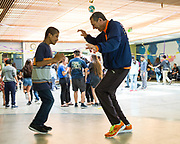 Milpitas High sophomore Mike Joshua Eronuevo, left,  dances with Adapted Physical Education Specialist Rod Heskett during the Best Buddies Special Education Dance at Milpitas High School in Milpitas, California, on April 21, 2017. (Stan Olszewski/SOSKIphoto)