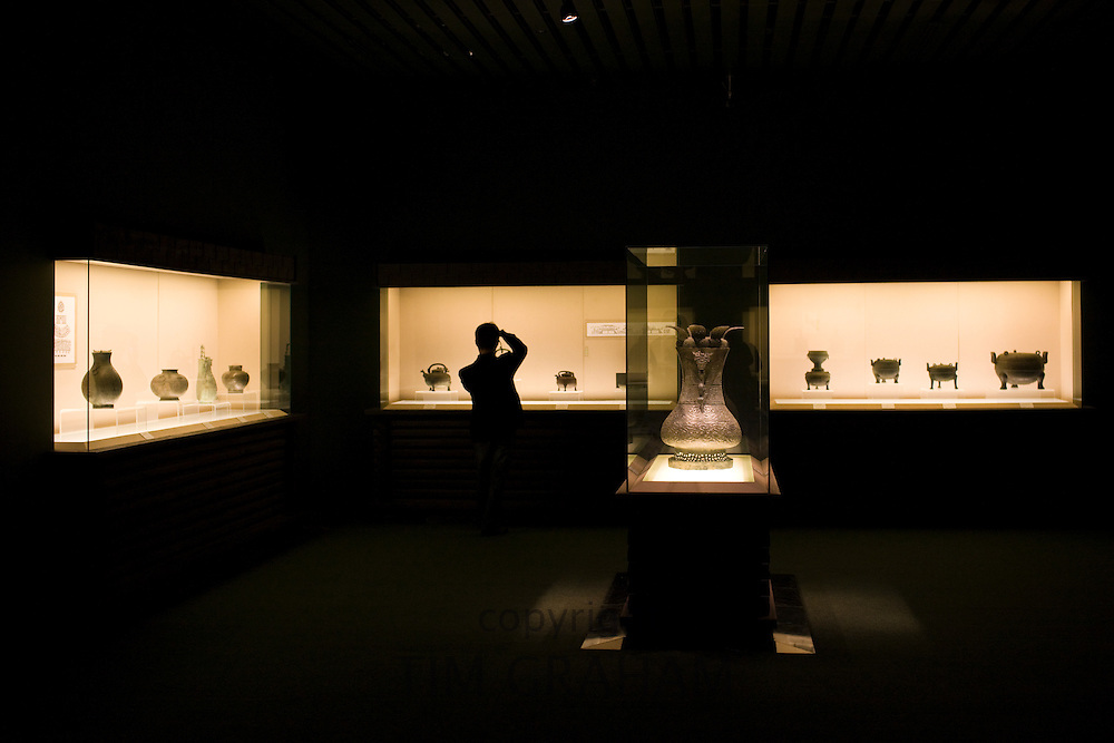 Visitor photographs bronze objects on display in glass case at the Shanghai Museum, China