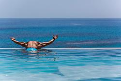 sexy man in an infinity pool overlooking the ocean in Bermuda