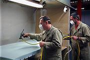 Nederland, Kesteren, 21-11-2007..Poolse arbeidskrachten verwerken schuimrubber tot een matras in de Recticel schuimrubberfabriek. Met lijm uit een luchtdrukspuit worden delen aan elkaar geplakt. Een computergestuurd productieproces waarbij olieproducten als grondstof dienen. Werknemers uit Polen werken in bijna alle sectoren van onze economie..Foto: Flip Franssen/Hollandse Hoogte