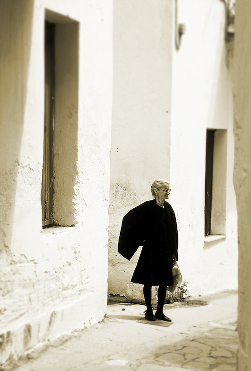 Old woman standing in alleyway on the island of Mykonos, Greece.