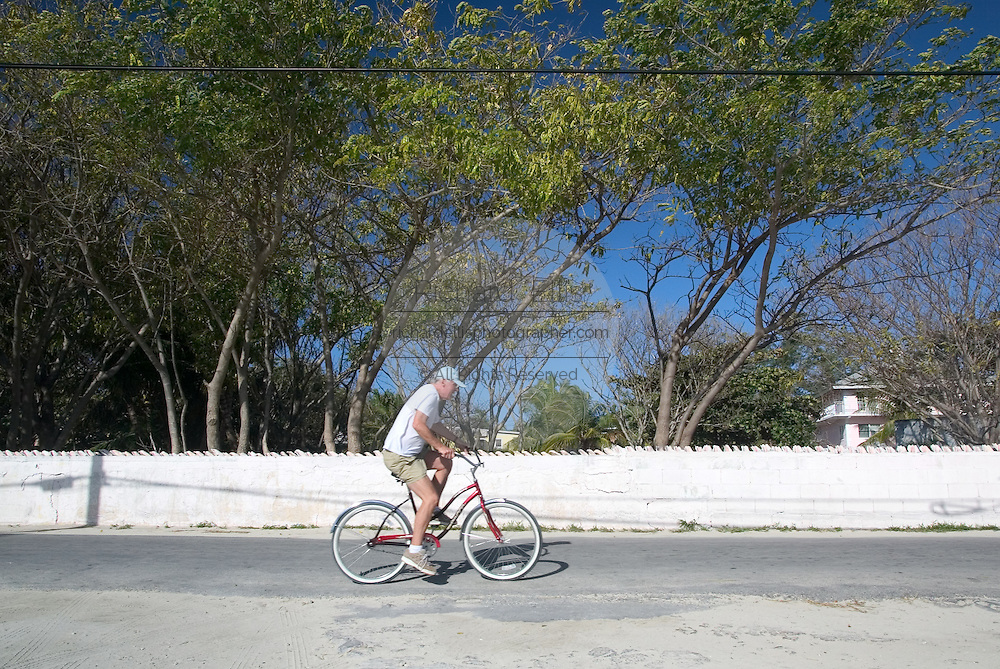 A tourist rides a bicycle along the King's Highway in Alice Town on the tiny Caribbean island of Bimini, Bahamas. Golf carts are the main form of transportation on the island.