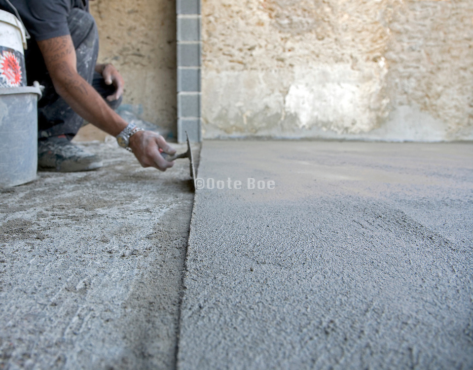 construction worker adding the finishing touch to a new floor